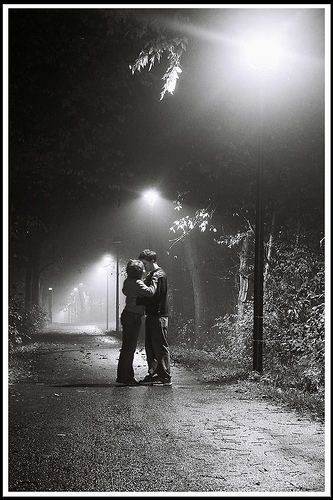 first kiss, black and white of teens kissing, kissing in the woods