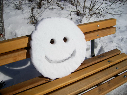 funny snow picture, smile in snow, round snow smile on a park bench